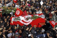Soldiers help mourners carry the coffin of slain opposition leader Chokri Belaid during his funeral procession towards the nearby cemetery of El-Jellaz, where he is to be buried, in the Jebel Jelloud district of Tunis February 8, 2013. REUTERS/Anis Mili