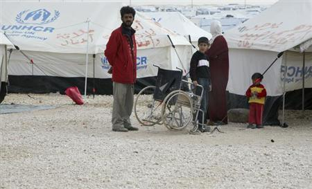 Syrian refugees stand outside their tent at the Al Zaatri Syrian refugee camp in the Jordanian city of Mafraq, near the border with Syria January 30, 2013. REUTERS/Majed Jaber