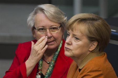 German Education Minister Annette Schavan (L) talks with Chancellor Angela Merkel during a session of the Bundestag, the German lower house of parliament, in Berlin October 18, 2012. REUTERS/Thomas Peter (GERMANY - Tags: POLITICS)