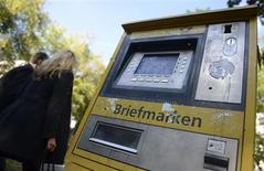 People pass a postal stamp vending machine in Hamburg October 1, 2012. REUTERS/Fabian Bimmer (GERMANY - Tags: POLITICS)