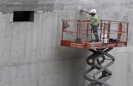 A construction worker polishes a cement wall on a building site in north London August 17, 2011. REUTERS/Suzanne Plunkett