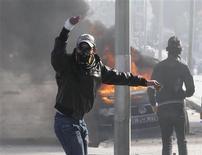 Un manifestante gesticula durante un enfrentamiento con la policía en las cercanías donde el líder opositor Chokri Belaid está enterrado en el distrito Jebel Jelloud de Túnez, feb 8 2013. Decenas de miles de deudos gritaban consignas anti-islámicas el viernes en Túnez durante el funeral del líder opositor secular Chokri Belaid, cuyo asesinato ha sumergido aún más al país en una crisis política. REUTERS/Louafi Larbi