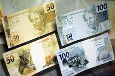 """Imagen de archivo de un anuncio con los nuevos billetes de 50 y 100 reales en Brasilia, feb 3 2010. La reciente apreciación del real brasileño ha sido """"algo exagerada"""", dados los fundamentos de la economía local y las expectativas sobre los movimientos de la moneda en el futuro, dijo el viernes a Reuters una fuente del equipo económico de la presidenta Dilma Rousseff. REUTERS/Ricardo Moraes"""