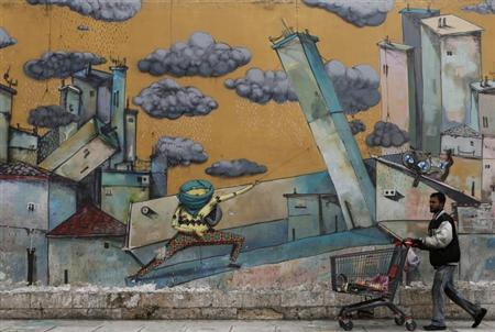 An immigrant living in Greece pushes a shopping trolley with scrap past a wall covered with a graffiti in Athens January 29, 2013. REUTERS/John Kolesidis