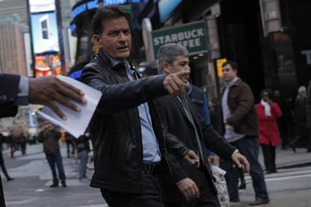 Actor Charlie Sheen (L) points to a pedestrian while he walks around Times Square in New York, January 14, 2013. REUTERS/Eduardo Munoz