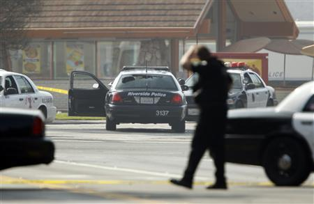 A police officer protects the scene, where two Riverside Police officers were shot while in their car (C), in the early morning in Riverside, California February 7, 2013. Authorities in California launched a manhunt on Thursday for a fired Los Angeles policeman who threatened ''warfare'' on cops and was suspected in a string of shootings that killed three people, one of them a police officer, and wounded two others. Former officer Christopher Dorner, 33, a U.S. Navy reservist who posted an online manifesto of his grievances, was suspected in an ambush shooting of two police officers in Riverside, 60 miles (100 km) east of Los Angeles, early on Thursday, killing one and critically wounding the other, police said. REUTERS/Alex Gallardo