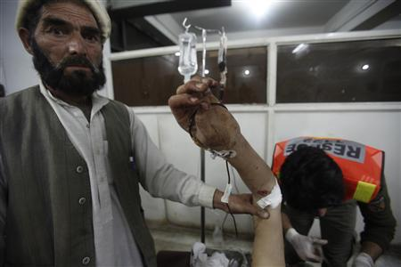 Rescue workers help a man who was injured during a suicide bomb attack in Kalaya, the capital of the semi-autonomous Orakzai Agency, in Peshawar February 8, 2013. REUTERS/Fayaz Aziz