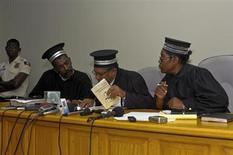 """Juízes que presidem o caso do ex-ditador haitiano Jean Claude """"Baby Doc"""" Duvalier revisam documentos legais num tribunal em Porto Príncipe, no Haiti, na quinta-feira. 07/02/2013 REUTERS/Swoan Parker"""