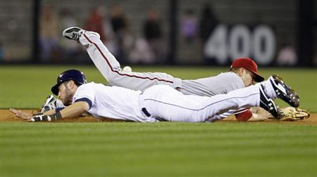 Arizona Diamondbacks' second baseman Aaron Hill (back) dives for the ball as San Diego Padres' right fielder Jeremy Hermida dives for second base, during a throwing error by Arizona Diamondbacks' catcher Miguel Montero (not pictured), in the seventh inning of their MLB National League baseball game in San Diego, California April 10, 2012. REUTERS/Mike Blake