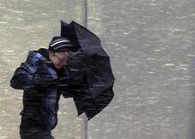 Una ventisca se cernía el viernes sobre el nordeste de Estados Unidos, acortando la semana laboral para millones de personas que temían quedarse bloqueados, mientras las autoridades ordenaban cerrar carreteras antes de la nevada, que según las previsiones podría superar récords. En la imagen, una mujer avanza protegíéndose de la nieve con un paraguas en Boston. REUTERS/Brian Snyder