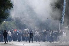 Decenas de miles de tunecinos se reunieron el viernes en el funeral del líder secular de la oposición Chokri Belaid, cuyo asesinato ha agudizado la crisis política del país del norte de África y generó violentas protestas contra el Gobierno liderado por islamistas. En la imagen, manifestantes se enfrentan a la polícía antidisturbios cerca del Ministerio del Interior, en Túnez, el 8 de febrero de 2013. REUTERS/Anis Mili