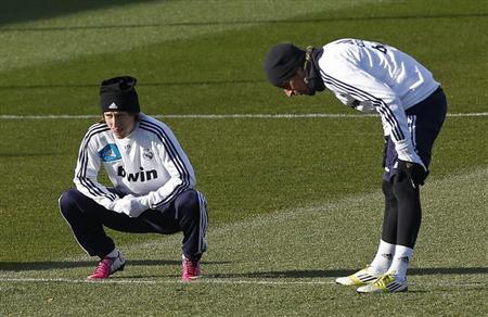 Real Madrid's Luka Modric (L) and Fabio Coentrao warm up during a training session outside Madrid January 14, 2013. REUTERS/Andrea Comas/Files