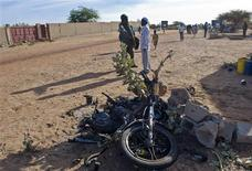 A soldier points his finger at the wreckage of a motorbike used by a suicide bomber who blew himself up at a checkpoint north of Gao, recently retaken from Islamist rebels, February 8, 2013. REUTERS/Francois Rihouay
