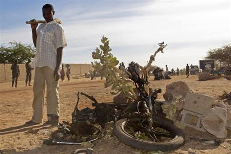 An inhabitant of Gao, inspects the wreckage of a motorbike used by a suicide bomber who blew himself up at a checkpoint north of Gao, recently retaken from Islamist rebels, February 8, 2013. REUTERS/Francois Rihouay