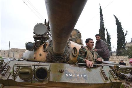 Free Syrian Army Fighters stand in a tank before heading to Wadi al-Deif, where clashes with forces loyal to Syria's President Bashar al-Assad are taking place in Idlib, February 6, 2013. REUTERS/Raed Al-Fares/Shaam News Network/Handout
