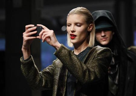 A model takes a photo with a smart phone as she presents a creation from the Kenneth Cole Autumn/Winter 2013 collection during New York Fashion Week in New York, February 7, 2013. REUTERS/Carlo Allegri