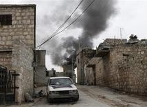 Smoke rises behind a car decorated with an Islamist flag in the Sheikh Saeed district, near a cement factory in Aleppo, February 7, 2013. REUTERS/Zain Karam