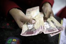 Imagen de archivo de una mujer pagando con bolívares en una tienda en La Guaira, Venezuela, ene 12 2010. El gobierno de Venezuela devaluó el viernes su moneda y fijó una nueva cotización para el tipo de cambio oficial de 6,3 bolívares por dólar, desde los 4,3 bolívares por dólar vigentes desde 2011. REUTERS/Jorge Silva