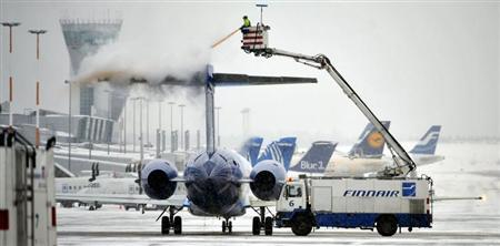 An employee of Finnish national airline Finnair sprays anti-freeze liquid on a Finnair passenger plane on the tarmac of Helsinki International Airport in Vantaa December 20, 2010. REUTERS/Jussi Nukari/LEHTIKUVA
