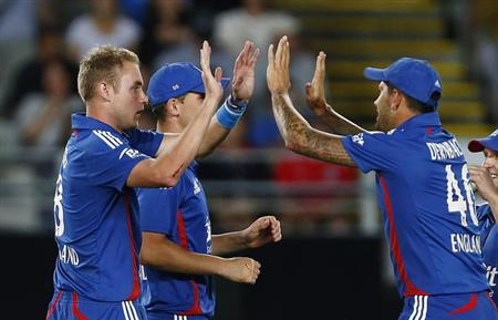 Team mates congratulate England's Stuart Broad (L) after he took a wicket during their first T20 cricket match against New Zealand at Eden Park in Auckland February 9, 2013. REUTERS/Simon Watts