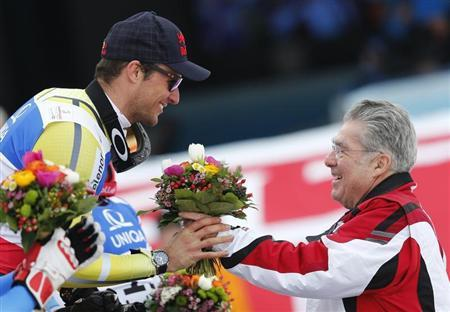 First placed Aksel Lund Svindal of Norway (L) receives a bouquet of flowers from Austria's President Heinz Fischer during the flower ceremony of the men's Downhill race at the World Alpine Skiing Championships in Schladming February 9, 2013. REUTERS/Leonhard Foeger