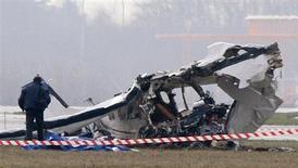 Um fotógrafo policial inspeciona os destroços de um avião de turistas no aeroporto de Charleroi, na Bélgica. 9/02/2013 REUTERS/Sebastien Pirlet
