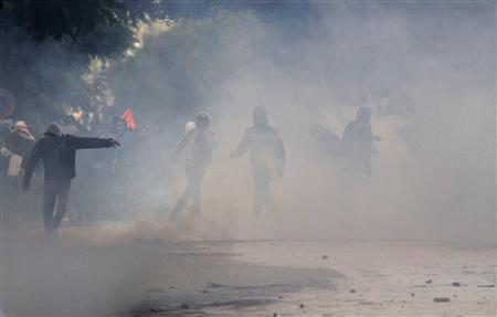 Protesters throw stones amidst smoke during clashes with riot police near the Interior Ministry in Tunis February 8, 2013. Tens of thousands of mourners chanted anti-Islamist slogans on Friday at the Tunis funeral of secular opposition leader Chokri Belaid, whose assassination has plunged Tunisia deeper into political crisis. REUTERS/Anis Mili