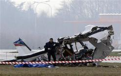 A police photographer inspects the scene of a tourist plane crash at Charleroi airport February 9, 2013. The small passenger plane crashed at Belgium's Charleroi airport on Saturday, killing five people and closing the international hub used by Ryanair and other low-cost carriers. REUTERS/Sebastien Pirlet
