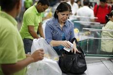Los venezolanos acudían el sábado a mercados y tiendas de electrodomésticos buscando anticiparse al nuevo tipo de cambio que imperará tras la devaluación anunciada por el Gobierno, que pretende oxigenar las finanzas del país acuciado por un elevado gasto público y una inflación feroz. En laimagen del 8 de febrero, una mujer guarda el cambio tras hacer la compra en un supermercado de Caracas. REUTERS/Jorge Silva
