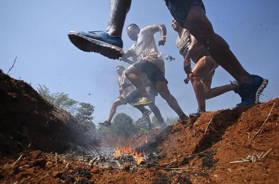 Competitors jump over a fire pit during the inaugural Mud Rush race in Kolad, 117 km (72 miles) south of Mumbai, February 9, 2013. The mud rush, the first event of its kind to be held in Asia, challenges competitors by making them negotiate a 7 km (4 mile) course strewn with obstacles including mud traps, barbed wire, streams and fire pits, organisers said. REUTERS/Vivek Prakash