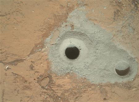 At the center of this image released to Reuters on February 9, 2013 from NASA's Curiosity rover is the hole in a rock called ''John Klein'' where the rover conducted its first sample drilling on Mars on February 8, 2013, or Sol 182, Curiosity's 182nd Martian day of operations. The image was obtained by Curiosity's Mars Hand Lens Imager (MAHLI) on Sol 182. The sample-collection hole is 0.63 inch (1.6 centimeters) in diameter and 2.5 inches (6.4 centimeters) deep. The ''mini drill'' test hole near it is the same diameter, with a depth of 0.8 inch (2 centimeters). REUTERS/ NASA/JPL-Caltech/MSSS/Handout