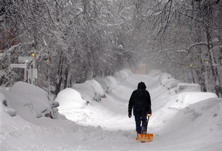 A man drags a shovel up Beacon Hill during a severe winter snow storm in Boston, Massachusetts February 9, 2013. A blizzard pummelled the Northeastern United States, killing at least one person, leaving hundreds of thousands without power and disrupting thousands of flights, media and officials said. REUTERS/Brian Snyder (UNITED STATES - Tags: ENVIRONMENT DISASTER)