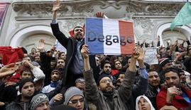 """Des manifestants islamistes brandissent samedi à Tunis l'inscription """"Dégage"""" en réponse aux propos du ministre français de l'Intérieur, Manuel Valls, qui juge que Paris doit """"soutenir les démocrates"""" en Tunisie. La démonstration de force des islamistes est également une réplique à la manifestation de vendredi lors des obsèques de l'opposant laïque Chokri Belaïd, dont l'assassinat a provoqué une onde de choc. /Photo prise le 9 février 2013/REUTERS/Zoubeir Souissi"""