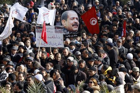 Tunisians hold a placard with an image of the late secular opposition leader Chokri Belaid during his funeral procession in the Jebel Jelloud district in Tunis February 8, 2013. REUTERS/Anis Mili