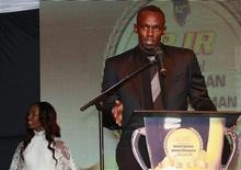 Jamaican Olympic sprinter Usain Bolt (R) speaks as Shelly-Ann Fraser-Pryce looks on after they were presented with the National Sportsman and Sportswoman of the Year awards, at the 52nd annual award ceremony in Kingston, January 11, 2013. Picture taken January 11, 2013. REUTERS/Gilbert Bellamy