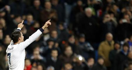 Real Madrid's Cristiano Ronaldo celebrates after scoring his third goal against Sevilla during their Spanish first division soccer match at Santiago Bernabeu stadium in Madrid February 9, 2013. REUTERS/Sergio Perez