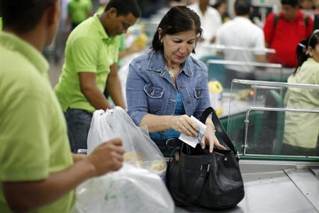 A woman leaves a supermarket after paying in Caracas February 8, 2013. REUTERS/Jorge Silva