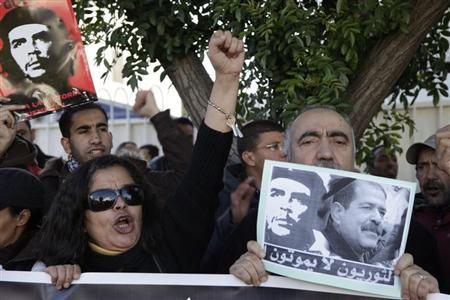 A Moroccan man holds a placard during a demonstration, against the killing of Tunisian secular opposition politician Chokri Belaid, in front of the Tunisian embassy in Rabat February 8, 2013. REUTERS/Stringer