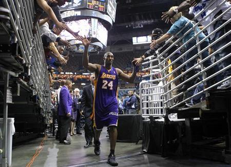 Los Angeles Lakers shooting guard Kobe Bryant (24) high fives fans as he leaves the court after their NBA basketball game against the New Orleans Hornets in New Orleans, Louisiana December 5, 2012. REUTERS/Jonathan Bachman/Files