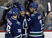 Vancouver Canucks Jordan Schroeder (C) congratulated by teammates Jannik Hansen and Mason Raymond after scoring his second goal of night against the Calgary Flames during the third period of their NHL hockey game in Vancouver, British Columbia February 9, 2013. REUTERS/Andy Clark