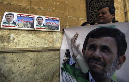 A man holds a banner of Iran's President Mahmoud Ahmadinejad in front of the Al-Hussein mosque, named after Prophet Mohammed's grandson Hussein ibn Ali, before Ahmadinejad's visit to the mosque in old Cairo February 5, 2013. REUTERS/Amr Abdallah Dalsh