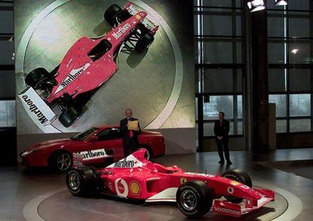 Rory Byrne reads his speech, as general manager Jean Todt (R) looks on, past the new Ferrari F1 Car F-2002 during the official presentation at Ferrari's headquarter in Maranello February 6, 2002. REUTERS/Vincenzo Pinto/Files