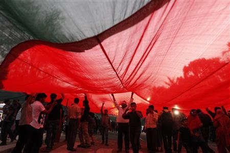 People walk under a massive national flag of Bangladesh as they attend a mass demonstration at Shahbagh intersection, demanding capital punishment for Bangladesh's Jamaat-e-Islami senior leader Abdul Quader Mollah, after a war crimes tribunal sentenced him to life imprisonment, in Dhaka February 9, 2013. REUTERS/Andrew Biraj