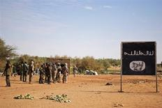 Malian troops secure the area where a suicide bomber blew himself up, next to an Islamist sign, in the northern city of Gao, Mali, February 10, 2013. Malian troops foiled a second suicide bomber attack in the northern town of Gao late on Saturday, highlighting fragile security in zones recaptured by a French-led offensive that is hunting Islamist insurgent bases further north. Malian Captain Sidiki Diarra told reporters that besides the bomber, who was blown to pieces, one Malian soldier was lightly wounded in the attack. REUTERS/Francois Rihouay (MALI - Tags: MILITARY CONFLICT)