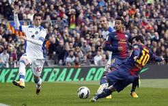 Lionel Messi, do Barcelona, chuta para o gol próximo a Thiago e Sergio Escudero, do Getafe, durante partida no estádio Camp Nou, em Barcelona, Espanha. 10/02/2013 REUTERS/Albert Gea
