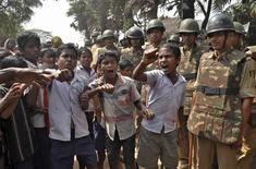 Children shout slogans as police stand guard during a protest against land acquisition at Gobindpur village in Jagatsinghpur district, in the eastern Indian state of Odisha, February 7, 2013. A few weather-beaten shipping containers, a swathe of sand and a bitterly divided village: that is all South Korea's POSCO has to show seven years after it announced plans for a $12 billion steel mill on a fertile strip of India's east coast. Despite the years of protests and battles over environmental clearances, Posco insists it is not about to throw in the towel. However, if a court ruling on access to local iron ore goes against it, that could push it over the edge. REUTERS/Stringer