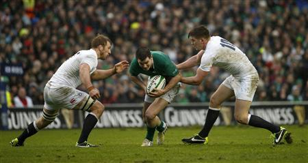 Ireland's Jonathan Sexton (C) is tackled by England's Chris Robshaw (L) and Owen Farrell during their Six Nations rugby match at the Aviva Stadium in Dublin February 10, 2013. REUTERS/Eddie Keogh