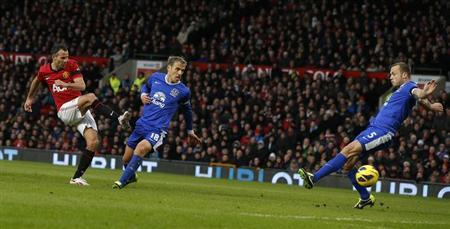 Manchester United's Ryan Giggs scores the opening goal past Everton's Phil Neville (C) and Johnny Heitinga (R) during their English Premier League soccer match at Old Trafford in Manchester, northern England February 10, 2013. REUTERS/Phil Noble