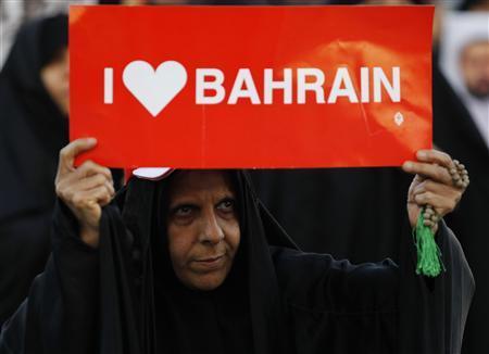 A protester holds a banner saying ''I Love Bahrain'' as she participates in a rally organised by Bahrain's main oppostion society Al Wefaq, in Budaiya, west of Manama, February 9, 2013. REUTERS/Hamad I Mohammed