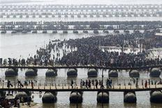 "Hindu devotees cross the river Ganges on pontoon bridges after bathing in the waters at Sangam - the confluence of the Ganges, Yamuna and mythical Saraswati rivers - after the second ""Shahi Snan"" (grand bath), during the ongoing ""Kumbh Mela"" or Pitcher Festival in the northern Indian city of Allahabad February 10, 2013. REUTERS/Jitendra Prakash"